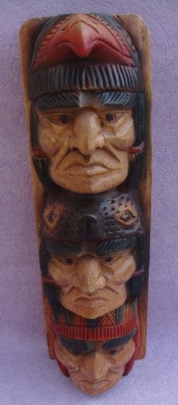 Un poteau en bois avec des têtes des indiens